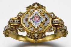 """Gold & Enamel Bracelet c1840, hinged, multi-colored enamel w/a pattern of flowers & scrolls, center accented w/roses, pansies & forget-me-nots on a white enamel ground. Hinged central compartment  for 18 karat gold pocket watch, case enameled in matching floral design, dial engraved w/flowers & scrolls, black Roman numeral chapter ring and moon-style hands, key wind movement, dust cover and case numbered 18997, the bracelet engraved """"Wednesday, Feb. 11, 1846″. Together with a watch key."""