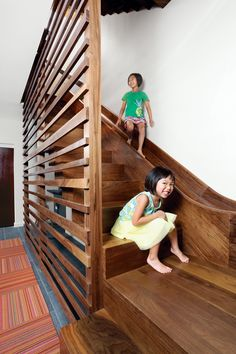 """The walnut staircase and slide in a Chicago town house leads from the main level to the basement. To protect people on the ride down, a """"crash pad"""" fashioned from a standard gymnastic mat covers the wall at the slide's base."""