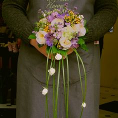 cottage garden style flowers in a hand tied posy .