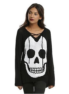 """<div>You can never have too many sweaters with skulls on them, especially if they're all slightly different. The black tunic length pullover has a large white skull design and a lace-up V-neck. Pair it with your favorite skinnies or some comfy leggings for the perfect outfit!</div><div><ul><li style=""""list-style-position: inside !important; list-style-type: disc !important;"""">100% acrylic</li><li style=""""list-style-position: inside !important; list-style-type: disc !important;"""">Wash cold; dry…"""