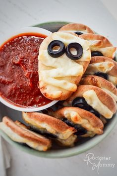 mini mummy pizzas stack in a bowl with red dipping sauce