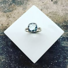 Handmade by David Ayling.Silver Ring set with a 10mm Cushion Cut Blue Topaz.The band measures approx 2.4mm wide and can be made to any size required.Please note this ring is handmade to order and delivery is approx. 3 weeks.