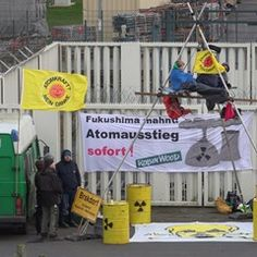Environmental activists Robin Wood fix a protest banner outside Brokdorf nuclear power plant