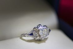 Diamond ring with sapphires accents in 14K white gold.