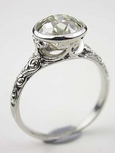 In this heavenly Edwardian antique engagement ring, an old European cut diamond is bezel set in a hand wrought and engraved platinum mounting. Weighing 2.06 carats, the diamond floats angelically above a scroll motif shank and under bezel. Like a golden orb of light, the diamond's cut and color maximizes its beauty under candlelight. Circa 1910. From the Topazery Tara Collection.  $12299.00