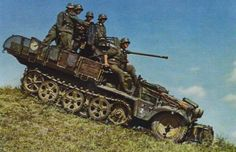 A German SdKfz. 10 halftrack vehicle mounting a 20-mm anti-aircraft gun driving down a hill with its crew aboard, date unknown