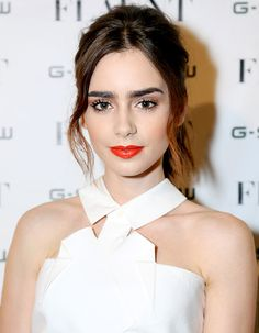 Lily Collins pairs her bold brows with an even bolder red lip
