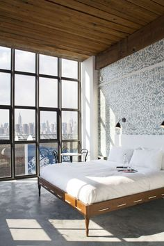 love the patterned wall, bed, lights... and of course that city view.
