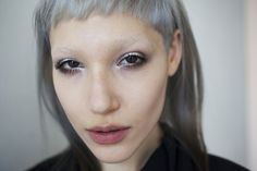 Silver micro fringe, very short baby bangs. Cut from the entire front section, tapered from brow length at temple to very short in the center. Long heart shaped face, large forehead. Edition 1 — Hairstory