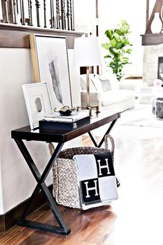 Chic foyer features a seagrass basket draped with a black and gray Hermes Avalon Blanket tucked under a dark stained x based console table topped with coffee table book and art. Foyer Decorating, Interior Decorating, Decorating Ideas, Hermes Blanket, Hermes Home, Black And White Interior, Black White, Duvet Sets, White Decor
