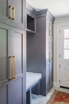 Floor to ceiling gray cabinets accented with brass pulls are fixed on either side of a gray shelf located over a gray built in bench finished with a white and gray cushion.