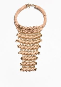 Rows of soft fabric ropes are contrasted by multiple gold-tone chains in this elegant statement necklace that sits close to the neck.