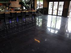 black stained concrete floors. A polished concrete floor with a black stain and white decorative joints  provides beautiful modern stained created by MODE CONCRETE in