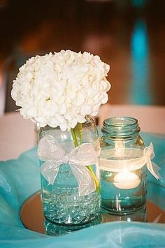 Centerpieces! Blue mason jar with hydrangea with other mason jar have water with floating candle! Tulle surrounding jars while jars on round mirror! www.angelajacksonphotography.com