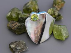 Black Lip oyster shell with a round faceted Peridot in a Wave Design. Adjustable Sterling Silver ring.