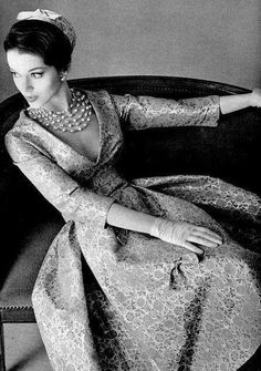 1957 Model is wearing a gold leaf brocade dress with a deep decolletage by Jean Patou and necklace by Scemama.: