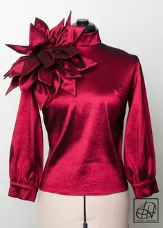 Available in all colors and sizes online or call 972-754-5096! Round neck blouse with key hole opening at neck, peplum at the waist, and back invisible zipper.