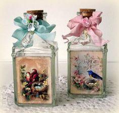 serviettentechnik auf glas   zwei flaschen, eine blaue und eine pinke schleife mit einer einer pinken rosaund zwei servietten mit zwei roten vögel und einem blauen vogel und zwei nestern