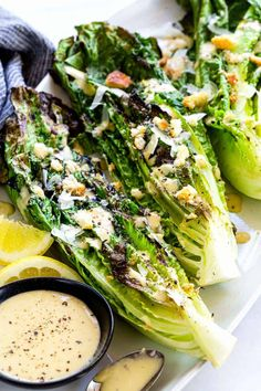 Grilled Caesar Salad with leafy sections of romaine seared on the barbecue to create a lightly charred texture then drizzled in homemade dressing.