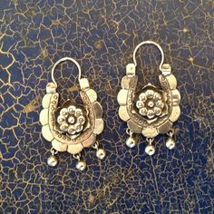 Lovely silver arracadas decorated with three small flowers and a small amount of filagree on the sides. Arracada earrings are meant to sit at a slight angle when they are in the ear--that's just the way they are made. It's a customary style worn in many regions of Mexico. This