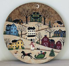 A horse drawn sleigh dashes across the countryside in this primitive winter landscape that has been hand painted on a wooden plate that measures about 11 1/2 inches in diameter.  Colorful saltbox houses dot the snow covered hills as the moon shines in the snowflake filled sky. A snowman, black cat and little brown dog watch the sleigh zip by. The plate is signed and the back is a mottled dark brown.  PLEASE NOTE: Each plate is individually hand painted to order. The one you receive may h...