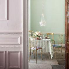 Pariser Stil Esszimmer. Akzente von Gold auf den Stühlen und Geschirr eine elegante Essbereich. Wählen Sie einen blassen Hintergrund für eine ruhige und einladende Atmosphäre, und gestreiften Tischwäsche fügt eine entspannte Note.