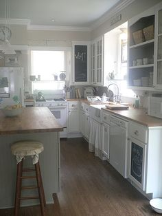 Sheetrock above cabinets. Farmhouse sink open and glass-front cupboards, butcher block counters and island.