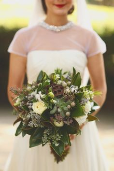 bouquet with magnolia leaves - photo by J.Woodbery Photography http://ruffledblog.com/alabama-wedding-with-a-vintage-inspired-bridal-party #weddingbouquet #bouquets #flowers
