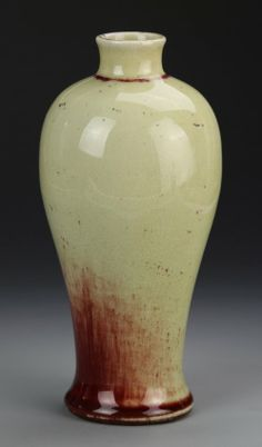 China, Yuan Dynasty, cream-glazed Meiping vase, high shoulder, narrow neck, red ring around neck and base, mottled red hues on body. Height 9 in.