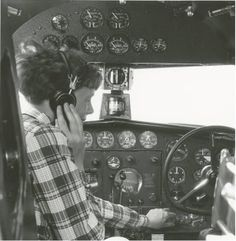 Amelia Earhart with headphones adjusting the controls in the cockpit of her Lockheed Electra.