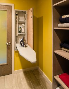 Small spaces: A built-in wall cabinet stores an ironing board, a power outlet, a steam connection and shelves. Plus, the outside of the door is a mirror.