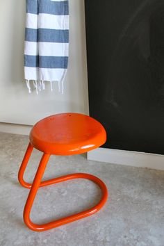 """I recently came across this adorable little vintage milking stool at a pop-up shop, and couldn't wait to get it home. I've been looking for a small step stool to live in my kitchen and this one is sturdy and balanced enough (it's stronger than it looks) for me to use as a quick """"leg up."""" When, I got it, the stool's paint was cracking and peeling, so I couldn't wait to get it home to put this glossy, new orange coat on it."""