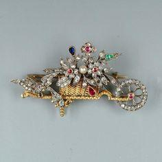 A diamond and gem set wheelbarrow brooch, circa 1890.