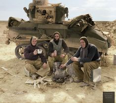 """The crew of a British Light Tank Mk.VIB having a """"brew up"""" and cooking their Christmas dinner beside their vehicle, in Libya, North Africa. 31st of December 1940. (note – they are sitting on fuel or water containers and using a cut in half, empty can (a """"flimsy"""" – the infamous 4-Gallon non-returnable petrol tin) for heating the food, referred to at the time as a """"Banghazi Fire"""". The tanker seated in the middle is holding a can of 'Pilsner Lager'.)"""