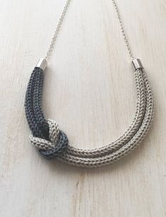 Necklace made entirely by hand with the technique of tricot using a yarn 100% cotton of excellent quality. The yarns used are pearl grey and dark grey. Perfect as a gift idea or as an accessory to wear for the holiday season. Adjustable hypoallergenic silver carabiner clasp. The total