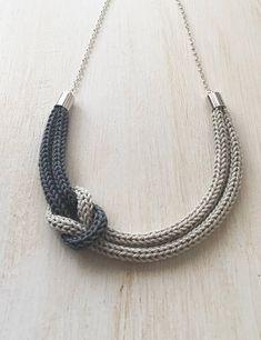 Collana realizzata interamente a mano con la tecnica del tricot utilizzando un filato 100% cotone di ottima qualità. I filati utilizzati sono di color grigio perla e grigio scuro. Perfetto come idea regalo o come accessorio da indossare per le festività natalizie. Chiusura con