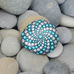This hand-painted rock is natural from the beaches of the French Riviera. It is painted black, with detailing in a mix of turquoise and metallic silver, with a lighter shade of turquoise to finish and each turquoise dot. The stone has been coated twice with a clear satin varnish.