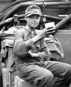 The war is over for him: 13-year old German army conscript enjoys a cup of coffee aboard a US landing craft taking him to England as a POW, June-July 1944.