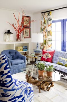 Colorful living room- love mixing prints, shades of blue, and that bold printed accent chair on left front.