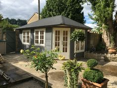 Large traditional corner garden studio, available in a variety of sizes and styles, painted in grey and white.