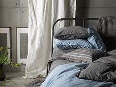 Nahaufnahme von einem Metallbett mit ÄNGSLILJA Bettwäsche-Sets in Hellblau und Grau