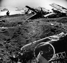 Marines fighting in the second Japanese airfield south of Iwo Jima, in the wreckage of Japanese destroyers, Nakajima Tenzan B6N the February 20, 1945. You can see the bottom of the image, landing craft and the invasion fleet.