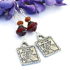 """The MINE handmade earrings are perfect for the woman who loves dogs. They feature fun, artisan handcast pewter charms with an incised dog and bone design with """"mine"""" stamped across the top. Ruby red Czech glass Saturn beads and reddish orange Czech glass beads add a huge pop of rich color."""