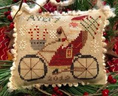 Homespun Elegance Avery's Cycling Santa - Cross Stitch Pattern. Model stitched over 2 threads on 30 Ct. Putty linen with DMC floss and Weeks Dye works floss. St