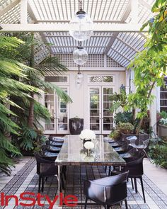 THE OUTSIDE PATIO The couple enjoys inviting friends over for casual dinner parties served buffet style, often under their white trellised p...