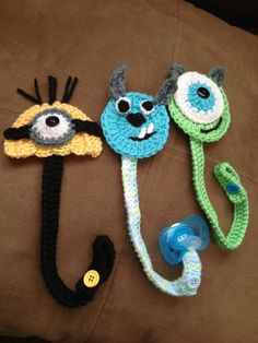 Baby pacifier clip holder crochet idea with monsters and minion for green, blue, black and yellow colors. Crochet Baby Bibs, Crochet Baby Booties, Love Crochet, Crochet Gifts, Crochet For Kids, Crochet Yarn, Crochet Toys, Baby Knitting, Yarn Projects