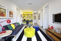 Clarendon Homes. Ascot 32. Rumpus with study nook, bright yellow feature wall and colourful furnishings.