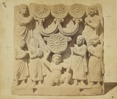 Photograph of a Buddhist sculpture slab from the lower monastery at Nutta in Peshawar District showing the worship of the triratna symbol.'This represents shaven-headed monks paying adoration to the Dharma-chakra, or symbol of the wheel, which is surmounted by the Triratna, or symbol of the ''three gems'', above which are three wheels, or Dharma-chakras. The Triratna is described as the triple object of veneration - Buddha, the law, and the church. The wheel symbol is the wheel of the law of…