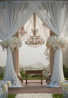We love the use of the dramatic chandeliers and soft draping to create a romantic altar that has style and vintage flair.