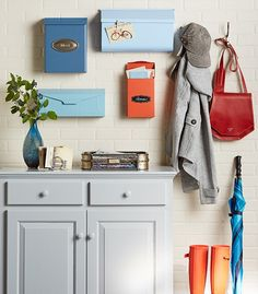 Create a drop zone for grab-and-go items. Paint assorted wall-mounted mailboxes for a unique way to organize your things. Garment hooks catch hats, coats, and bags. Then keep your entry floor clean and dry on a boot mat made from a water heater drip tray filled with gravel. It works for wet umbrellas, too.